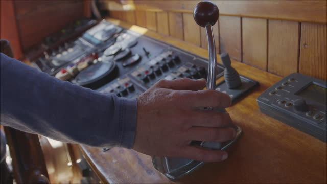 helmsman driving a sailboat. close up of a man's hands operating the rudder and the lever at the ship cockpit. - lever stock videos & royalty-free footage