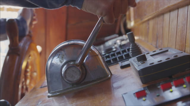 Helmsman driving a sailboat. Close up of a man's hands operating the rudder and the lever at the ship cockpit.