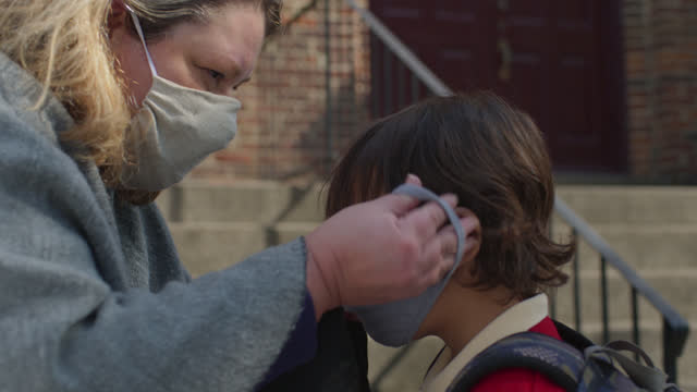 helpful mother helps her son take off his helmet and put on protective face mask before sending him off to school - single mother stock videos & royalty-free footage