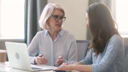 Helpful old female teacher mentor teach intern student with laptop