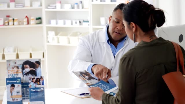 helpful pharmacist gives customer immunization information - flyer leaflet stock videos and b-roll footage