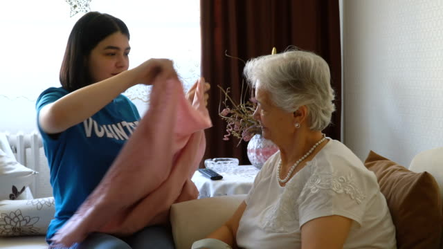 helpful young volunteer covering aged lady with blanket in home - covering stock videos & royalty-free footage