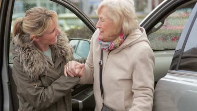 vídeos de stock e filmes b-roll de helping a senior woman out of the car - support