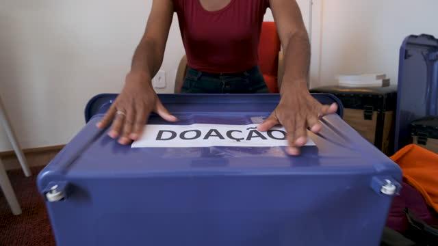 vídeos y material grabado en eventos de stock de ayudar a organizaciones benéficas con ropa usada. - sólo mujeres jóvenes