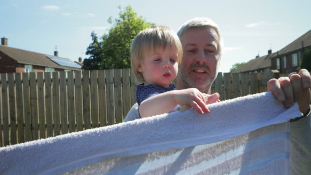 helping dad hang up the washing - day in the life stock videos & royalty-free footage