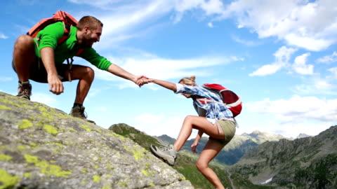 vidéos et rushes de aider la main entre deux grimpeur-été - motivation