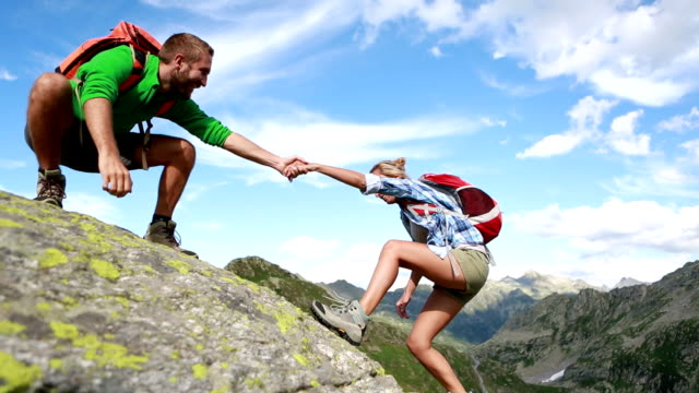 helping hand between two climber-summer - heterosexual couple stock videos & royalty-free footage