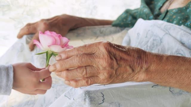 vidéos et rushes de un coup de main. petite fille part fleur avec grand-mère. - gestes