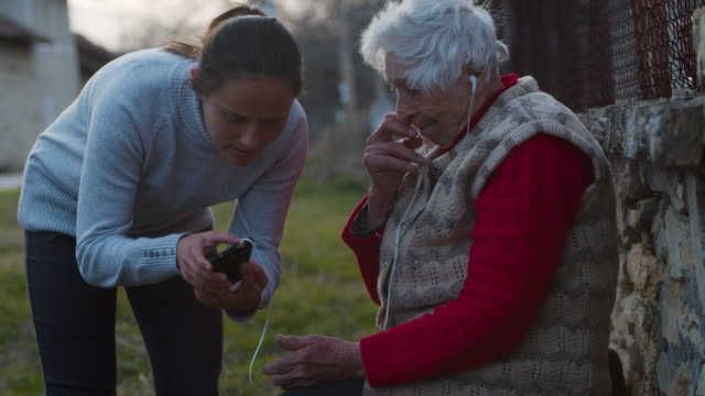 a helping hand. young woman explaining her grandmother how to listen to music with a set of headphones and a phone. - showing stock videos & royalty-free footage