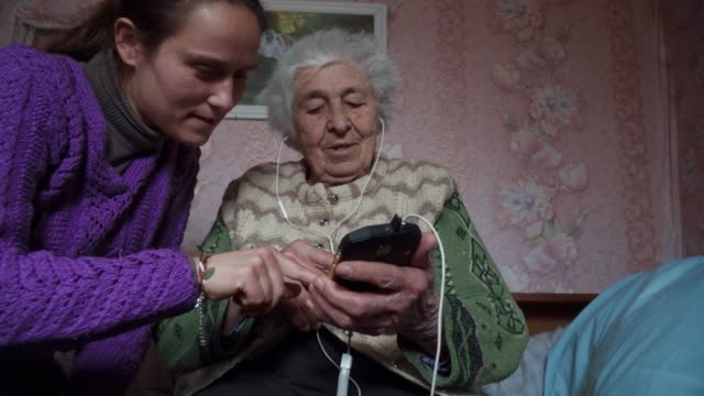 helping hands. a young adult helping a senior person to listen to music with a set of headphones and a phone, entertainment, medium shot portrait of a grandmother, wrinkles, enjoying the music, dancing with the rhythm, fun, rose background. - headphones stock videos & royalty-free footage