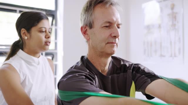vídeos de stock, filmes e b-roll de ajudá-lo a recuperar sua força. - fisioterapeuta