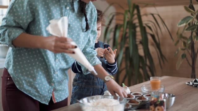 seiner mutter zu helfen, um muffins zu machen - backen stock-videos und b-roll-filmmaterial