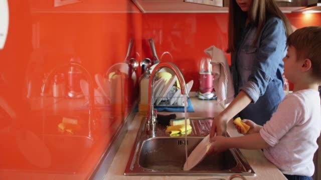vídeos y material grabado en eventos de stock de ayudar a mamá con los platos - son