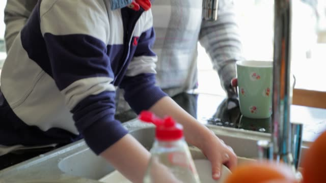 helping mum wash the dishes - washing up stock videos and b-roll footage