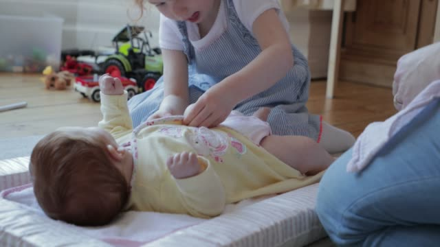 helping mummy change her baby sister's nappy - nappy bag stock videos & royalty-free footage
