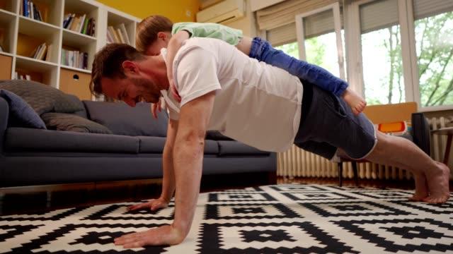 helping the daddy to exercise - allenamento a corpo libero video stock e b–roll