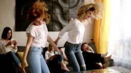Hen party. Group of six attractive girls are having fun. Two girls are dancing in craziness. Identical casual clothes. Emotionally moved. Indoors. Slow motion