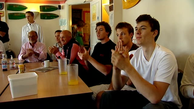 henley int britian supporters at leander rowing club watching olympic coverage on television and cheering on british men's coxless fours victory ivor... - canottaggio senza timoniere video stock e b–roll