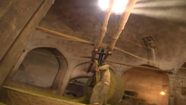 henna factory. low angled view of a mazari or mill worker shoveling as a stone grinds henna into powder. yazd is famous for the quality of its henna. - yazd province stock videos & royalty-free footage