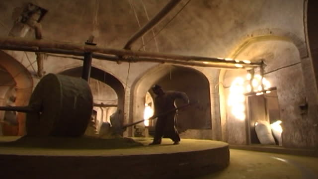 henna factory. low-angle view of a mazari or mill worker shoveling as a stone grinds henna into powder. yazd is famous for the quality of its henna. - yazd province stock videos & royalty-free footage