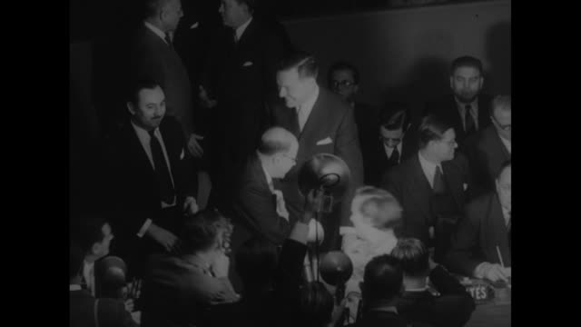 Henry Cabot Lodge Jr sits at US desk at the UN then pan to Andrei Vishinsky at USSR desk / full shot members at Security Council desk / Lodge shakes...