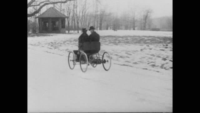 henry ford and clara bryant ford driving in early car - the quadricycle - on snow covered road, michigan, usa - ヘンリー・フォード点の映像素材/bロール