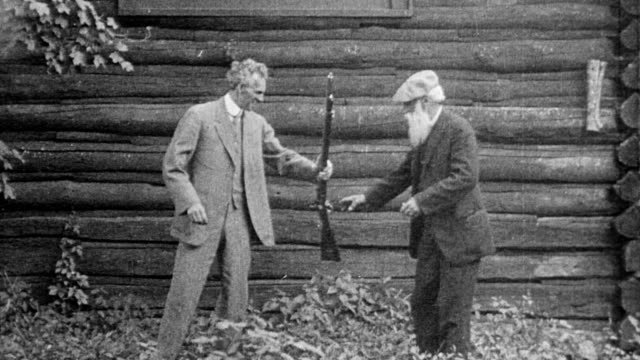 henry ford and naturalist john burroughs / ford firing rifle then handing it to burroughs - 1916年点の映像素材/bロール