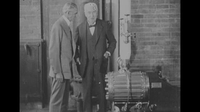 vídeos y material grabado en eventos de stock de henry ford and thomas edison share a laugh inside the reproduction of edison's menlo park lab at greenfield village at the light's golden jubilee... - michigan