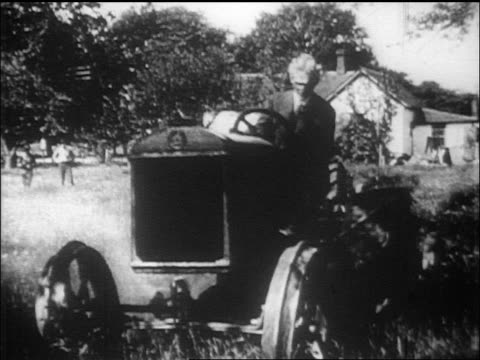 henry ford driving tractor in shady field / house in background / documentary - einzelner senior stock-videos und b-roll-filmmaterial