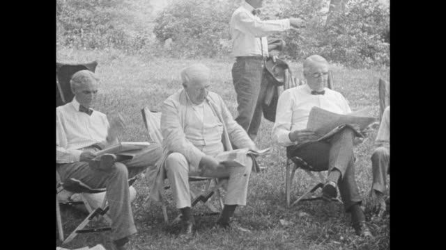 Henry Ford having lunch with naturalist author John Burroughs and Thomas Edison inside tent / US President Warren Harding visiting Ford entourage...