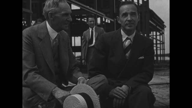 henry ford, holding a straw boater hat, with a man at a construction site; camera operator bearing a camera walks behind the two / note: exact day... - ヘンリー・フォード点の映像素材/bロール