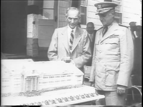 henry ford looks down at cake shaped like naval training school in dearborn michigan on his 80th birthday / sailors march by cake / ford mingles with... - フォード・t型モデル点の映像素材/bロール