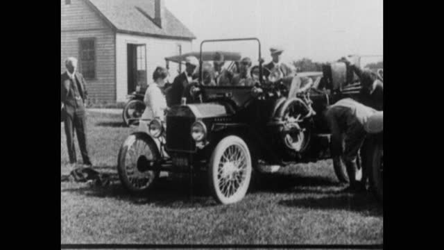 henry ford, men and women standing in garden by car, usa - ヘンリー・フォード点の映像素材/bロール