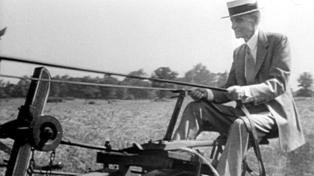 henry ford riding horse drawn plow in farm field / picking up harvested wheat / riding ford tractor - フォード点の映像素材/bロール