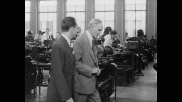 henry ford talking with another man while walking in factory with workers working in background, michigan, usa - ヘンリー・フォード点の映像素材/bロール