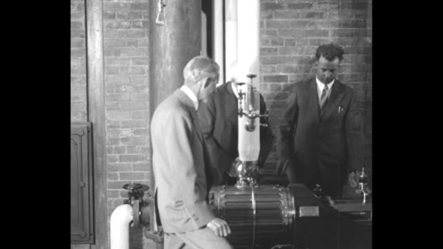 henry ford watching his friend thomas edison preparing to start engine with help of man next to him; ford and man leave and edison turns crank... - ヘンリー・フォード点の映像素材/bロール