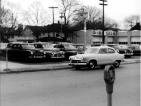 henry j corsair turns a corner and parks in front of the local kaiserfrazer new car dealer a man and woman get out and walk toward the front door... - henry j. kaiser stock videos and b-roll footage