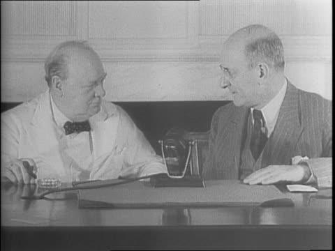Henry Morgenthau Jr and Winston Churchill sitting together / closeup of hundred dollar War Bond / Morgenthau speaking to Churchill and handing him a...