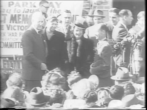 Henry Morgenthau Merle Oberon and Eleanor Roosevelt stand before a bank of microphones / a crowd watches / Morgenthau presents James Deveraux with a...