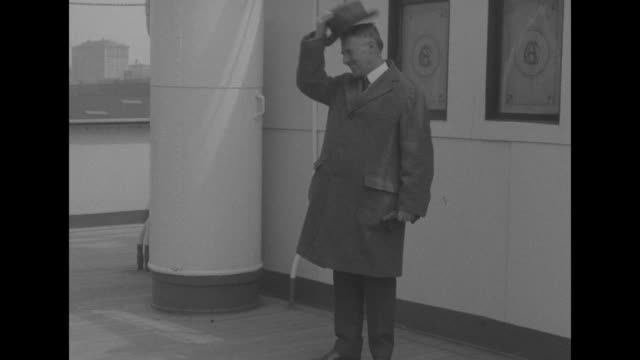 Henry Stimson wearing an overcoat and standing on a ship deck he smiles and doffs his hat gloves in hand / CU Stimson talking / Note [exact month/day...
