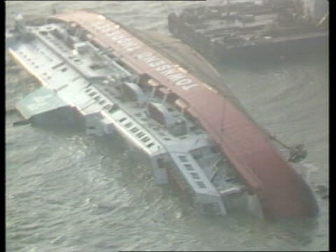 stockvideo's en b-roll-footage met details of disaster belgium zeebrugge l across length of capsized ferry ms bow salvage vessel on left zoom in steps on ferry - zeebrugge