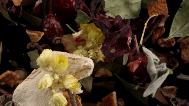 herbal tea ingredients in the air on black background - dried food stock videos & royalty-free footage