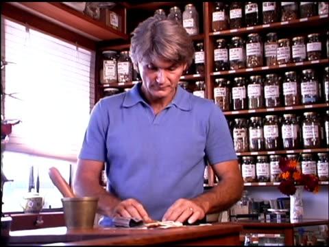 vidéos et rushes de herbalist preparing organic herbs - un seul homme d'âge mûr