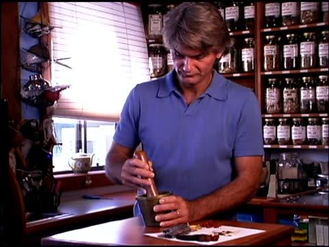 herbalist preparing organic herbs - one mature man only stock videos & royalty-free footage