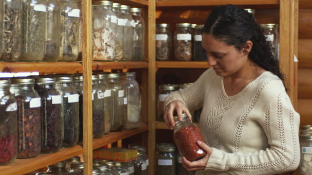 vidéos et rushes de ms herbalist smelling herb out of jar on shelf in shop / manchester, vermont, usa - manchester vermont