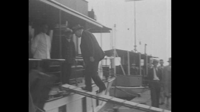 Herbert Hoover and small group and wife Lou walk on pathway with overhanging palm trees / the party walks to gangplank and boards yacht / long shot...