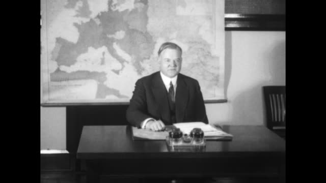 vídeos de stock e filmes b-roll de herbert hoover photo op with him seated at a desk with a map of europe behind him an aide brings him paperwork he dips his pen into an inkwell and... - presidente dos eua