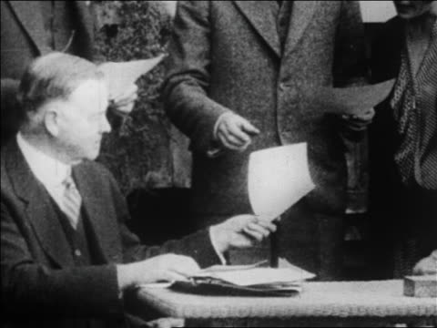 vidéos et rushes de herbert hoover sitting at table handing someone paper / newsreel - 1928