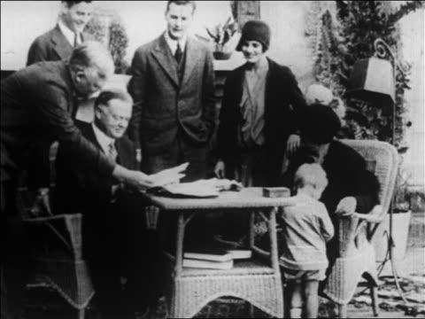 herbert hoover sitting at table smiling / group of people behind him / newsreel - 1928 stock-videos und b-roll-filmmaterial