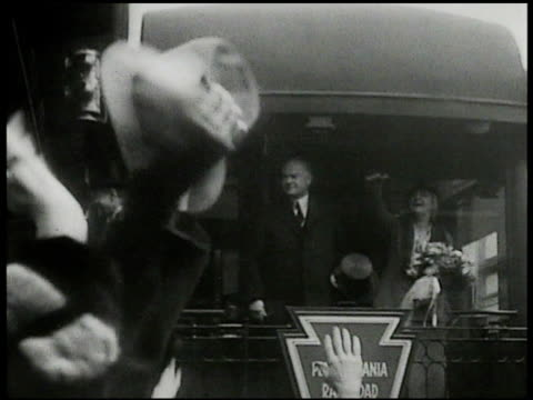 Herbert Hoover standing on back of Pennsylvania railroad train car w/ wife 'Lou' Henry Hoover waving to people as train pulls out of station